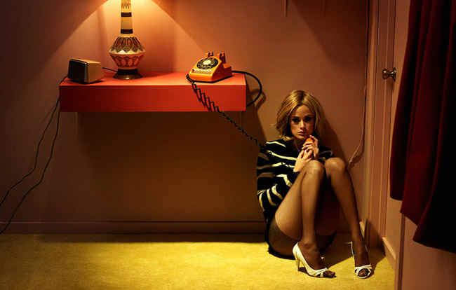 Woman by the phone in red room